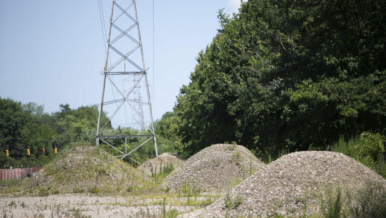 Dirt mounds with a cell tower and trees in the background.