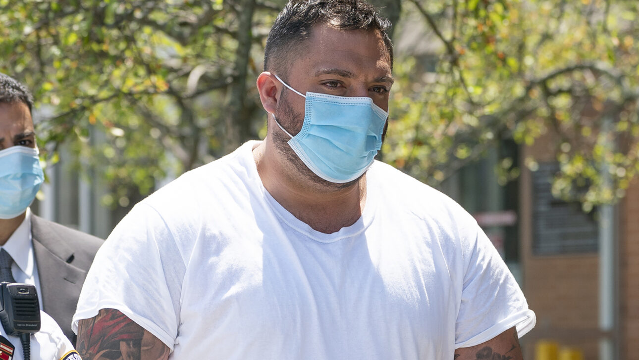 A man in a white t-shirt and blue medical mask.