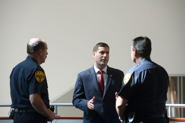 Tim Sini speaking with two cops.