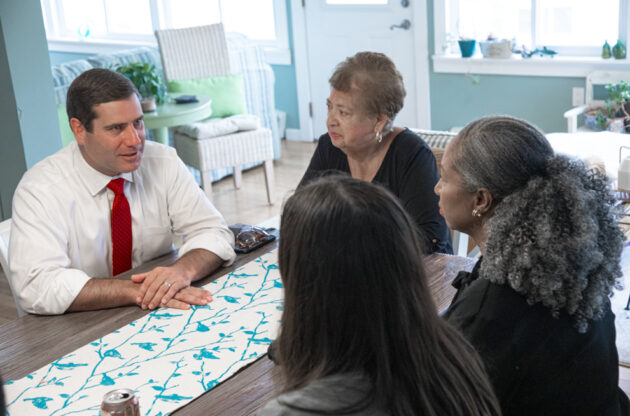 Tim Sini at a table, talking with three women.