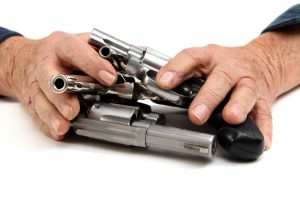 Two hands covering several guns.