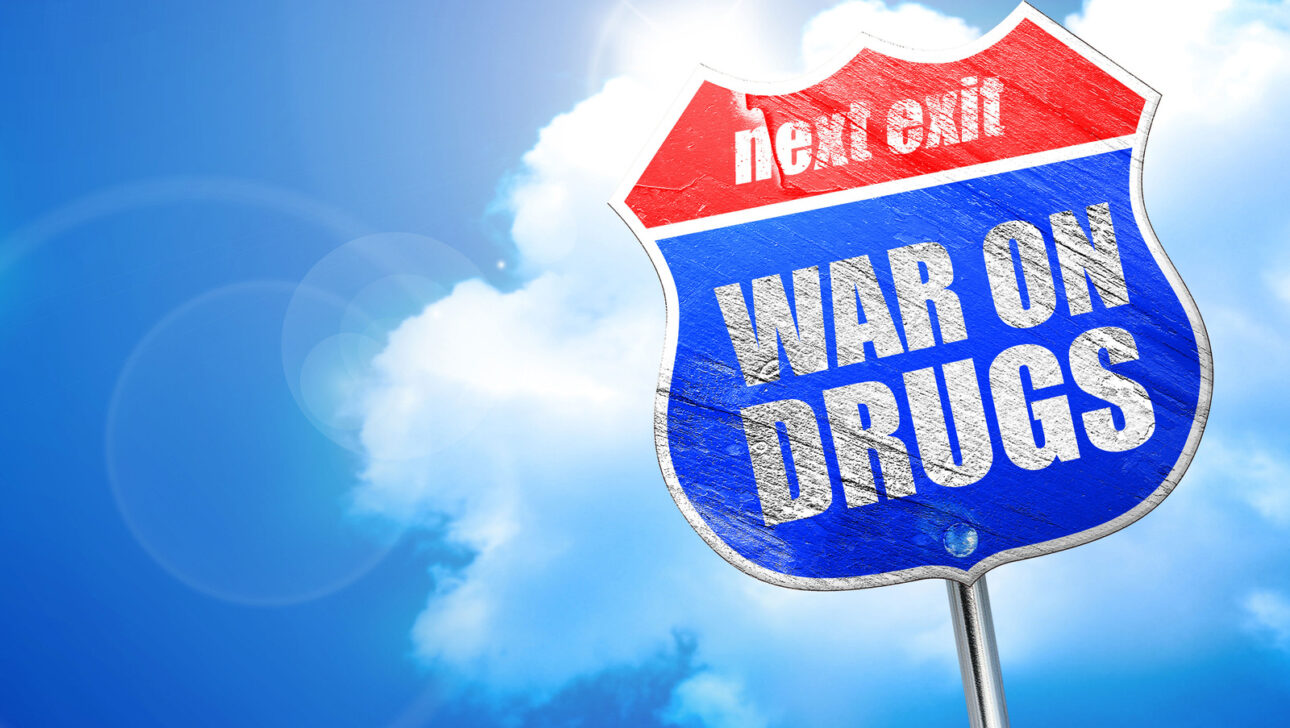 """A red and blue exit sign that reads, """"WAR ON DRUGS""""."""