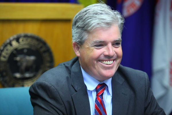 A man wearing a suit, smiling.