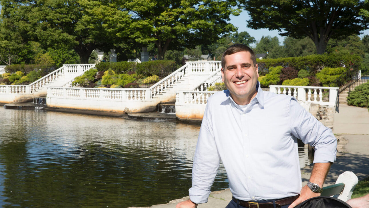 Tim Sini smiling in front of a pond with white stairs in the background.
