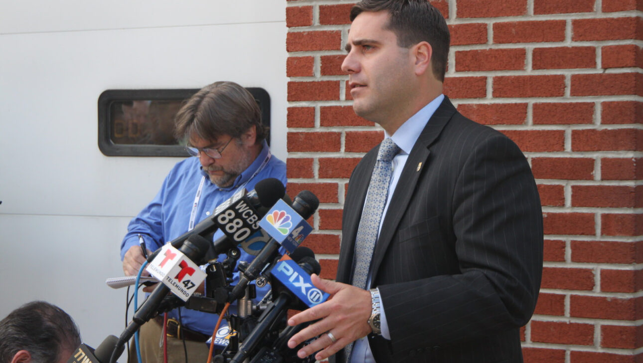 Tim Sini speaking at a news conference, along with a man taking notes in the background.