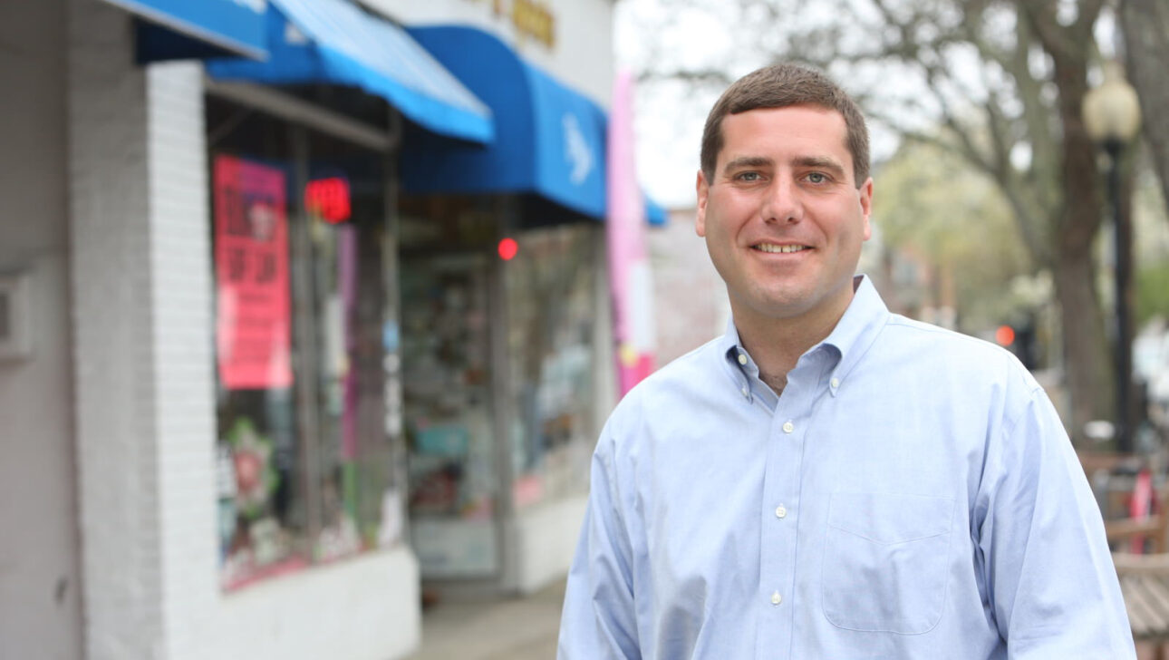 Tim Sini smiling in front of the outside of a store.
