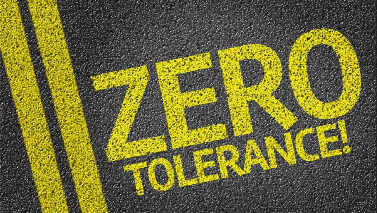 """""""ZERO TOLERANCE!"""" written in yellow on a road."""