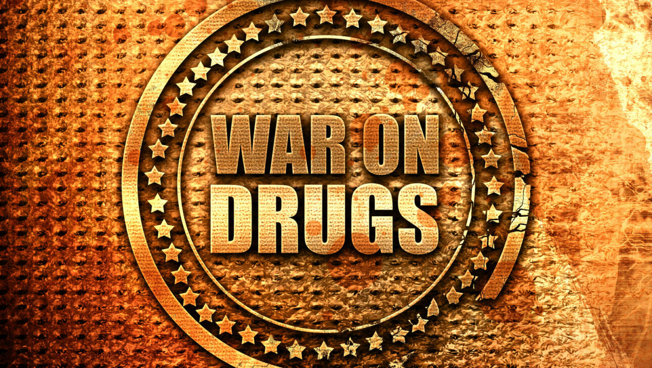 """A metal stamp with the words, """"WAR ON DRUGS""""."""