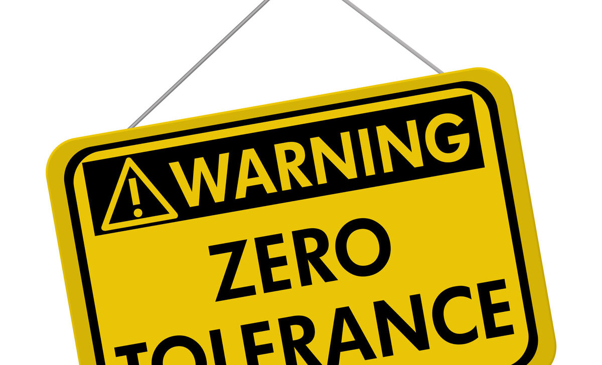 """A yellow warning sign that reads, """"ZERO TOLERANCE""""."""