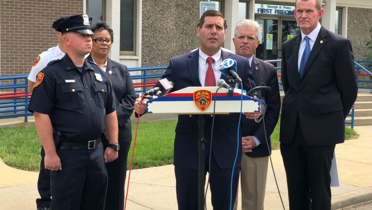 Tim Sini speaking to press alongside a police office and other officials.