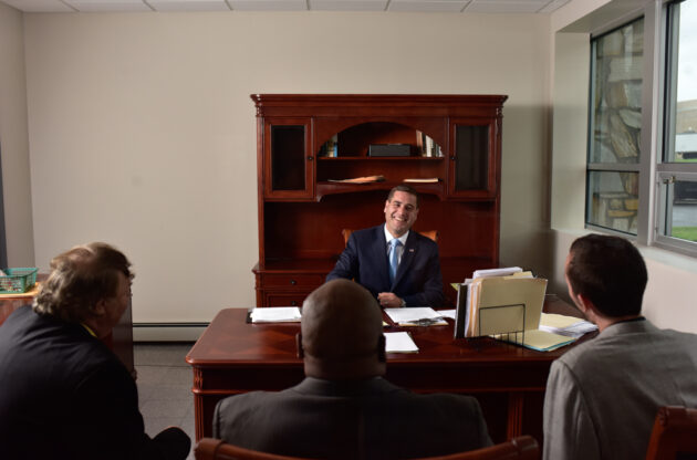 Tim Sini smiling at his desk in front of three people.