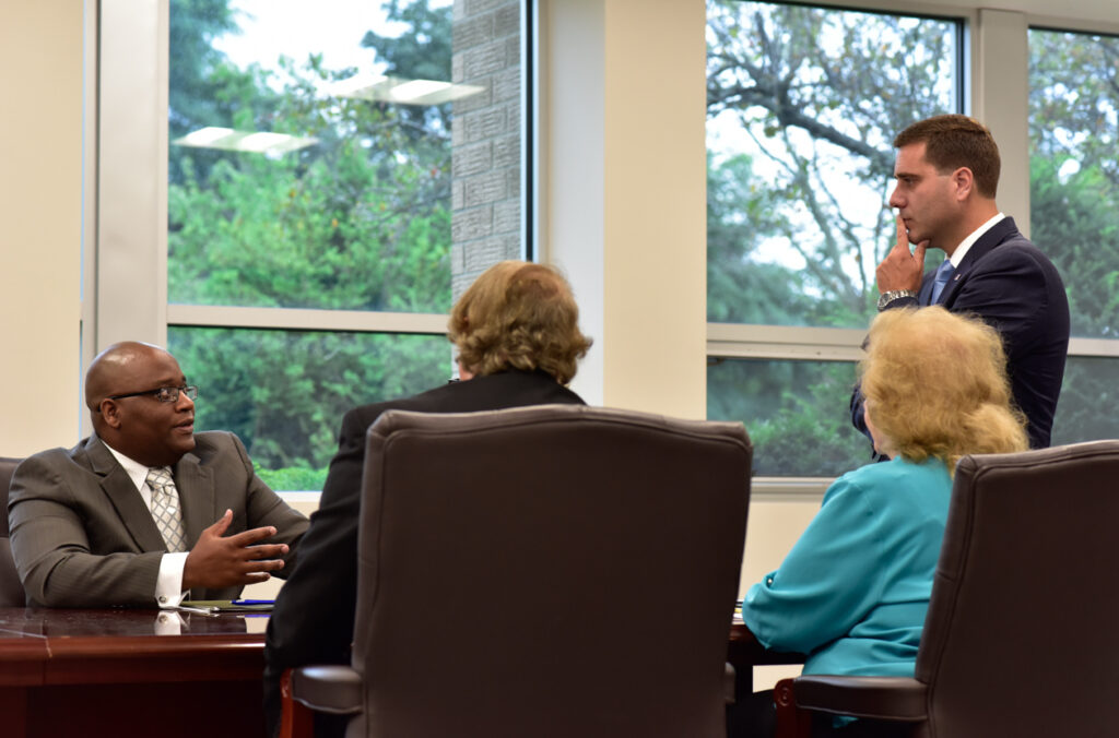 Three people sitting at a conference table, discussing something as Tim Sini stands near the table.