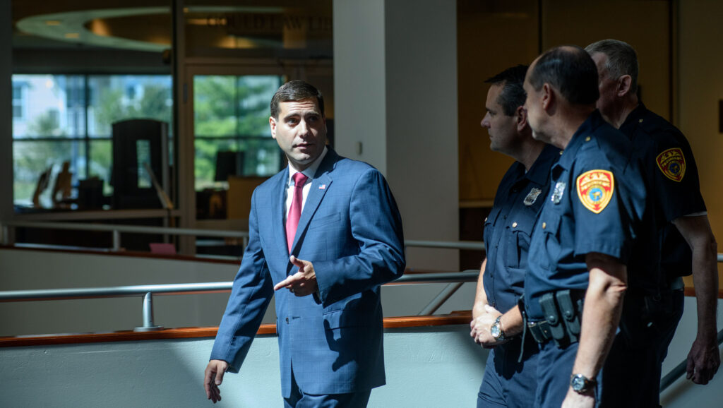 Tim Sini walking with three police officers.
